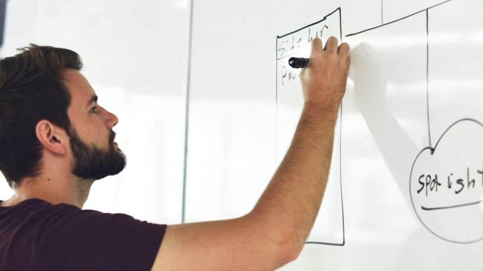 Boy writing on white board