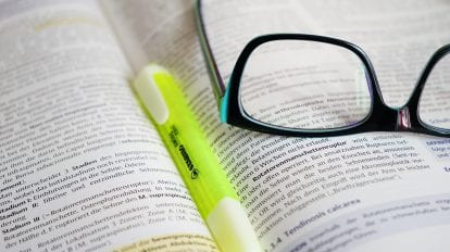 Glasses and a highlighter marker over a book
